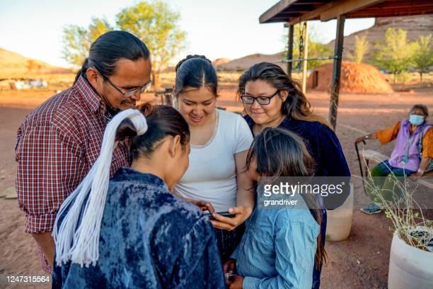 スマートフォンから写真を共有する時間を過ごすナバホ家族 - ナバホ文化 ストックフォトと画像