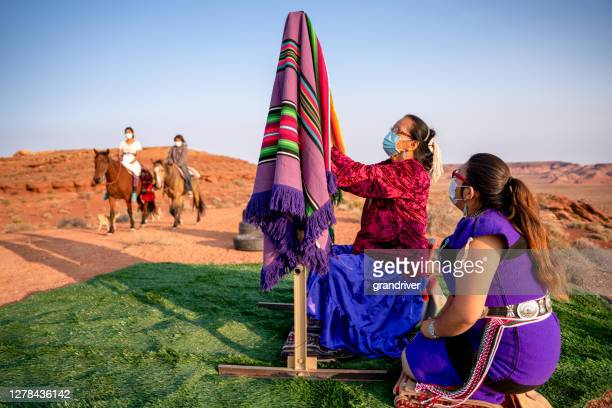 navajo grandmother teaching her granddaughter how to weave a traditional blanket on a loom outside in the desert in the northern arizona monument valley tribal park at dusk - apache stock pictures, royalty-free photos & images