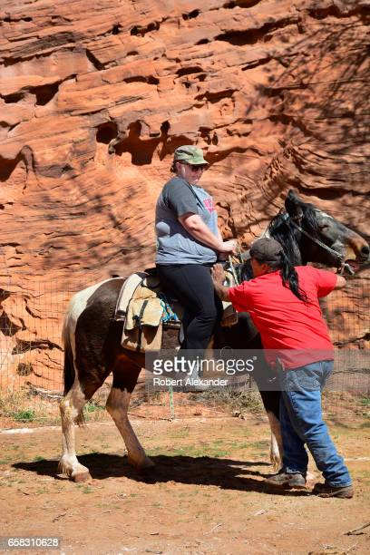 Navajo guide pushes a horse into position before taking a souvenir photograph of a young woman participating in a horseback tour at Canyon de Chelly...
