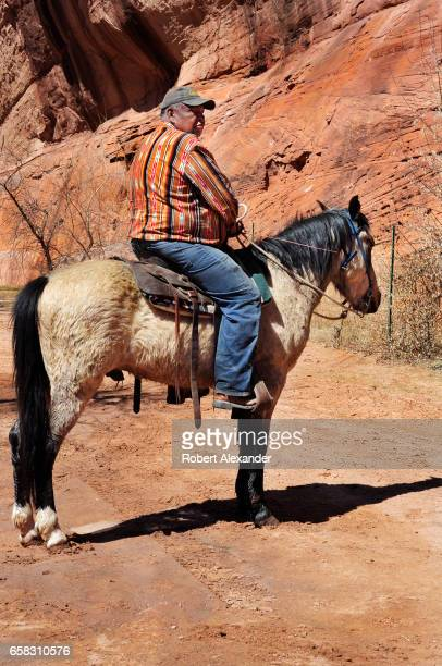Navajo guide sits on his horse at a rest stop during a horseback tour at Canyon de Chelly National Monument near Chinle Arizona Tourists can visit...