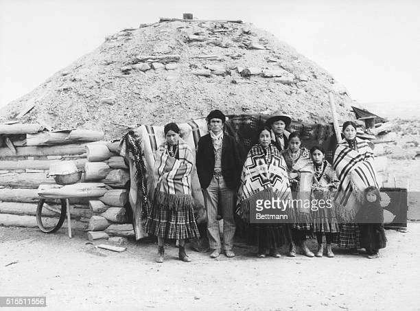Navajo Indian family wrapped in blankets standing outside their sod hut Undated photograph