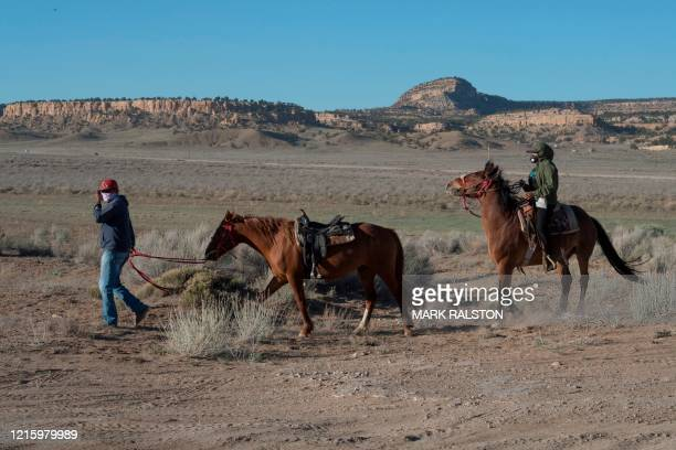 Navajo Indians riding their horses, arrive to collect water and supplies from a distribution point, as the Covid-19 virus spreads through the Navajo...