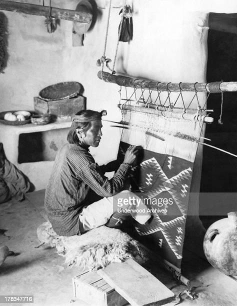A Navajo man sits at his loom weaving a blanket American Southwest c 1920