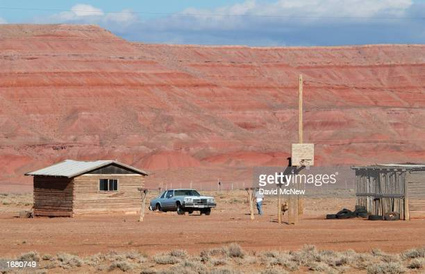 Navajo man walks to a small log house at Round Rock December 5 2002 on the Navajo Indian Reservation Arizona Tha Navajo Nation rejects the casino...