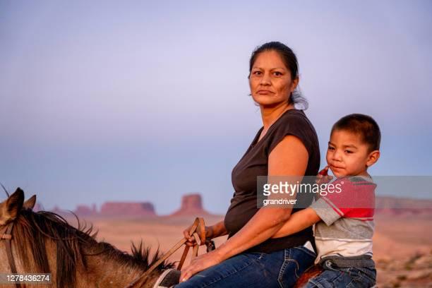 navajo mère et jeune fils de quatre ans posant à cheval devant les buttes dans le parc tribal de vallée de monument dans le nord de l'arizona au coucher du soleil - apache photos et images de collection
