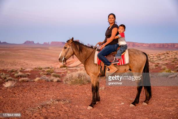 navajo mother and young four year old son posing horseback in front of the buttes in the monument valley tribal park in northern arizona at sunset - cherokee indian women stock pictures, royalty-free photos & images