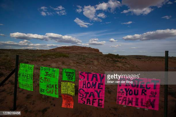 Navajo Nation residents post signs on a fence at their property line during the 57-hour stay-at-home order on the Navajo Reservation on Saturday, May...