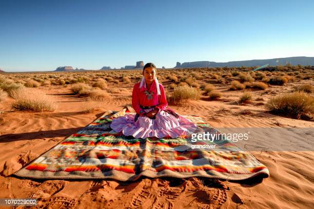 navajo native american teenage girl outdoor portrait on traditional blanket in desert - monument valley tribal park stock photos and pictures