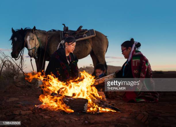 navajo siblings around a small bonfire with horses on monument valley - arizona - navajo culture stock pictures, royalty-free photos & images