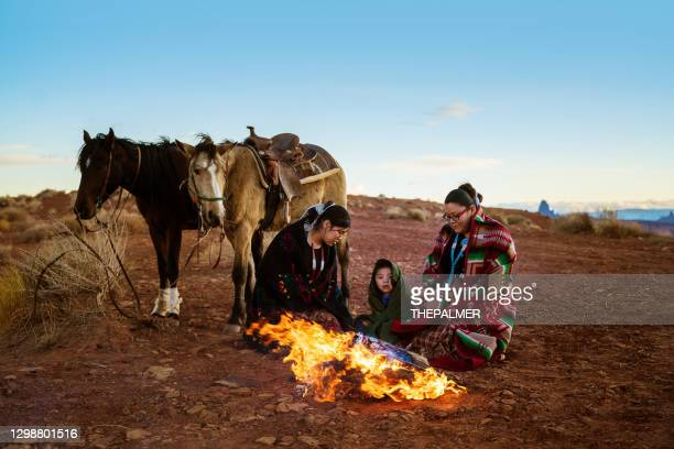 navajo siblings getting warm around campfire at sunset on monument valley - arizona - navajo culture stock pictures, royalty-free photos & images