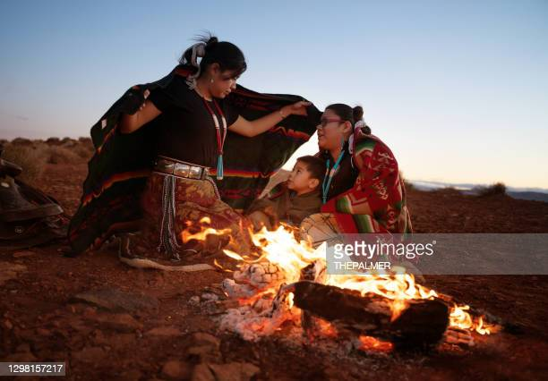 navajo siblings warming up around campfire at sunset - navajo culture stock pictures, royalty-free photos & images
