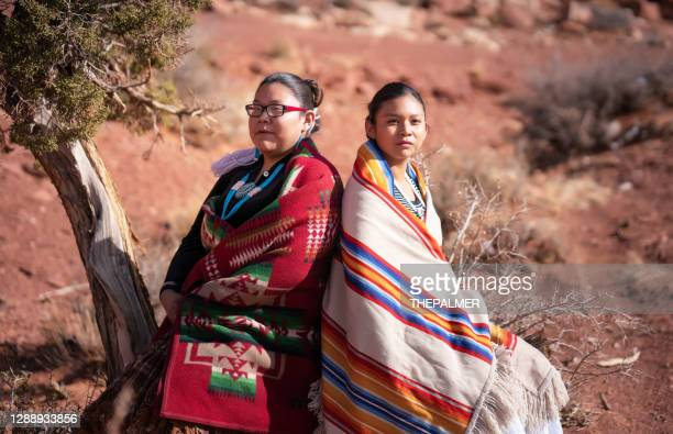 navajo sisters beside a cedar tree in monument valley tribal park - navajo culture stock pictures, royalty-free photos & images