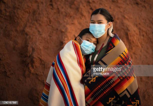 navajo sisters with face mask in front comforting each other during covid-19 quarantine - navajo culture stock pictures, royalty-free photos & images