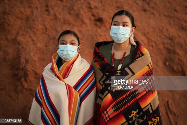navajo sisters with face mask in front of  their family hogan during covid-19 quarantine - indigenous north american culture stock pictures, royalty-free photos & images
