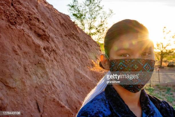 マスクを着用したナバホ10代の少女は、太陽が沈むにつれて彼女の家族のホーガンのそばに立っています - ナバホ文化 ストックフォトと画像