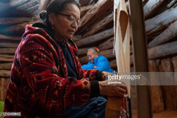 a navajo woman weaves a saddle blanket on a loom, her mother in the background - minority groups stock pictures, royalty-free photos & images