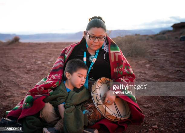 navajo young woman holding a traditional drum with little brother around campfire on the arizona desert - navajo culture stock pictures, royalty-free photos & images