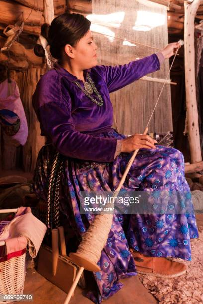 Navajo young woman weaving sheep wool