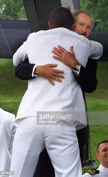 Naval Academy graduate Kevin Terrel gives US President George W Bush a bear hug after receiving his diploma May 25 2001 in Annapolis MD Bush made...
