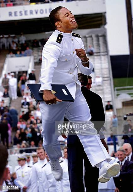 S Naval Academy graduate Kevin Young jumps high in the air after receiving his diploma from US President George W Bush at the US Naval Academy...