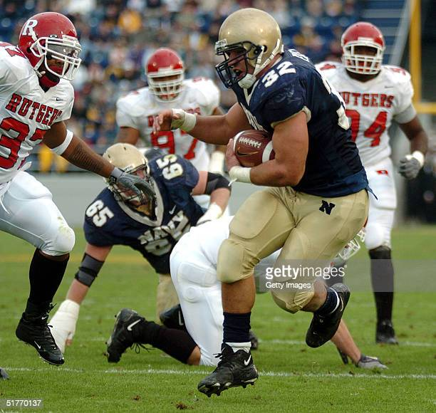 S Naval Academy Midshipman 1st Class Kyle Eckel breaks through a line of Rutgers University Scarlet Knights defenders enroute to a touchdown in the...