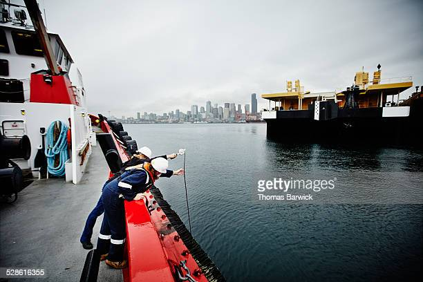 Naval architects measuring freeboard of tugboat