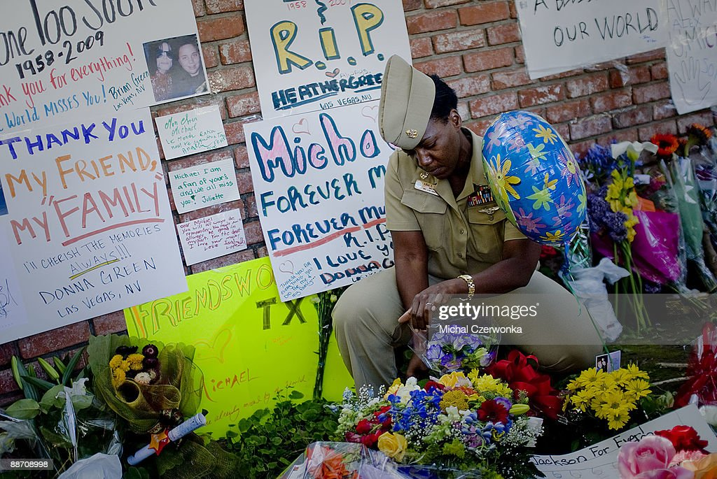 Naval Chief Petty Officer Lisa L. Jack places flowers at a makeshift memorial outside the Jackson family compound on June 26, 2009 in Encino, California. Jackson, 50, the iconic pop star, died after going into cardiac arrest in a hospital yesterday in Los Angeles, California.