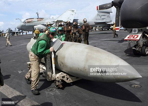 US naval crew push a droptank of an F16 fighter plane on the US supercarrier USS Kitty Hawk in the Bay of Bengal during the Malabar exercise 07...