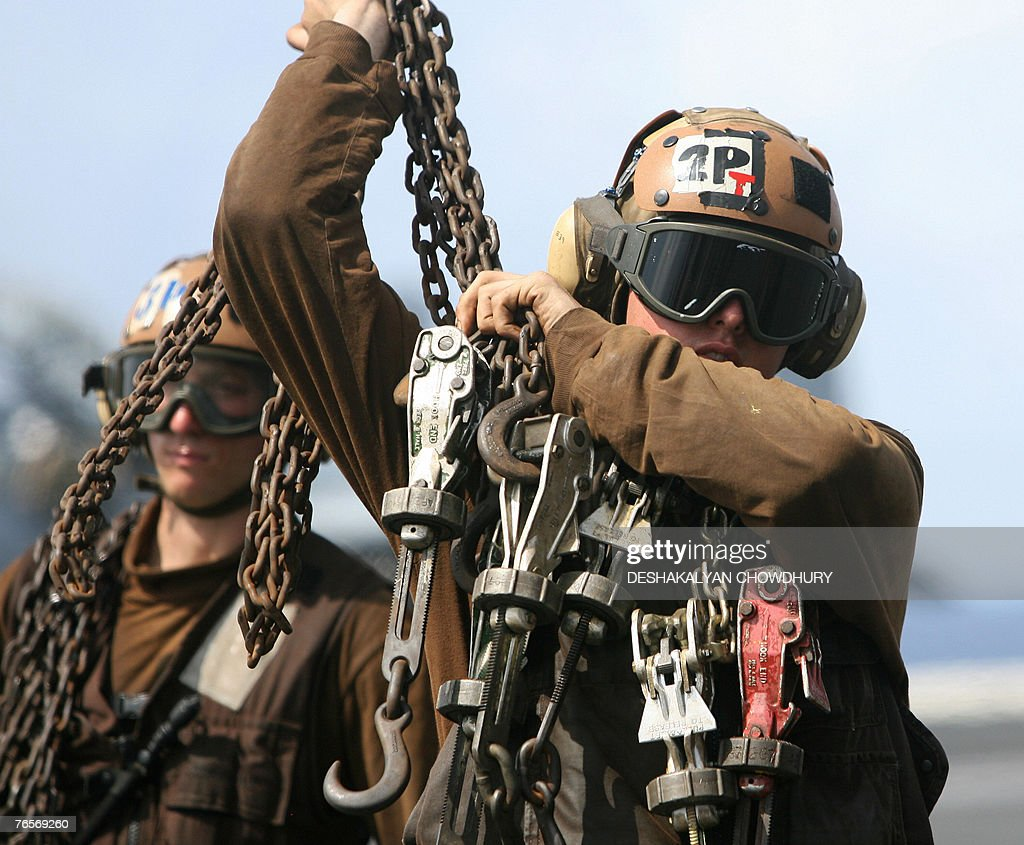 A US naval crew-member holds the tow chains on the US super-carrier USS Kitty Hawk in the Bay of Bengal, during the Malabar exercise, 07 September 2007. Twenty-seven ships and submarines from the United States, Australia, Japan and Singapore have joined seven from host India off the Andamans archipelago in the Bay of Bengal for six-day manoeuvres in the international exercises, codenamed Malabar, which started on the 04 September. AFP PHOTO/Deshakalyan CHOWDHURY