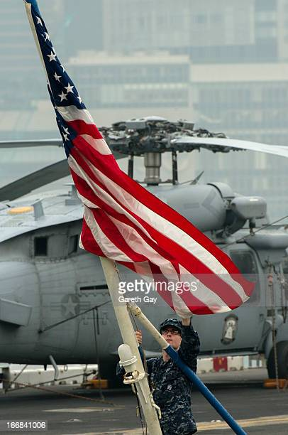 A naval officer adjusts the American flag aboard the USS Peleliu during it mooring at Tsim Sha Tsui on April 16 2013 in Hong Kong The amphibious...