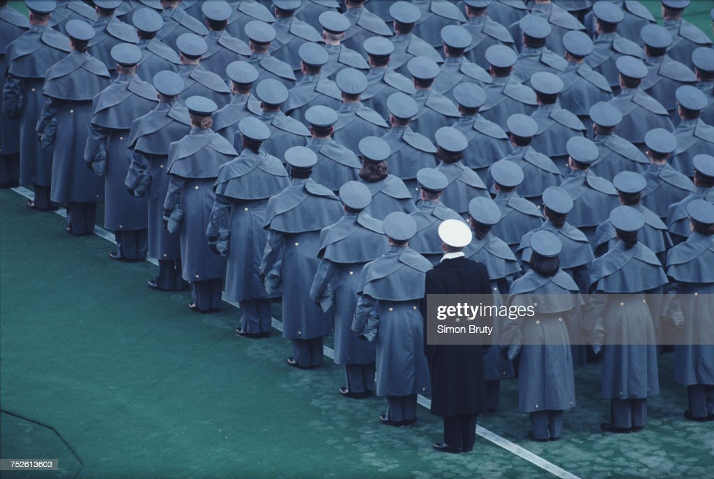 A naval officer from the United States Naval Academy at Annapolis stands with cadets from the United States Military Academy at West Point during the parade before the NCAA Army-Navy college football game on 4 December 1994 at the Veterans Stadium, Philadelphia,Pennsylvania, United States. Army won the game 22–20.
