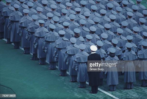A naval officer from the United States Naval Academy at Annapolis stands with cadets from the United States Military Academy at West Point during the...