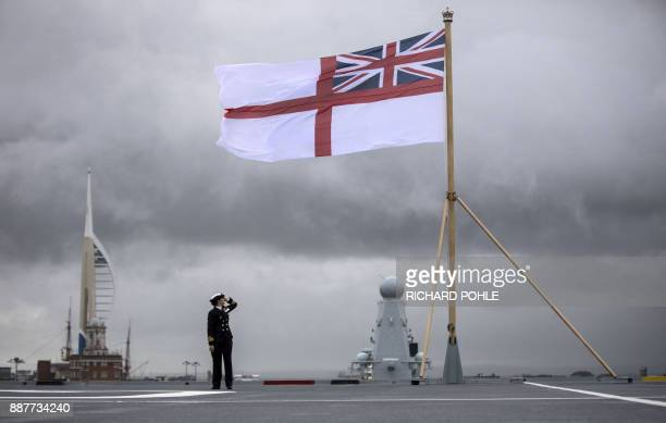 A naval officer looks up at the fluttering White ensign flag hoisted at the stern during the Commissioning Ceremony for the Royal Navy aircraft...