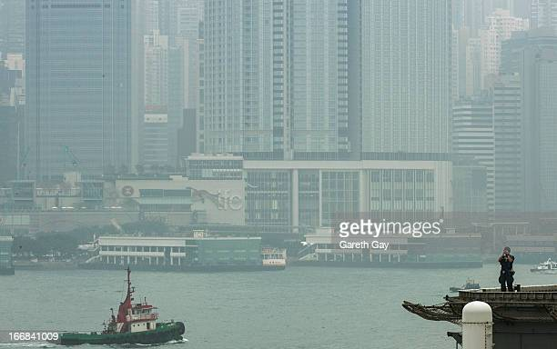 Naval officer patroling the deck looks out over the harbor aboard the USS Peleliu during its mooring at Tsim Sha Tsui on April 16 2013 in Hong Kong...