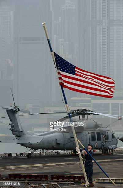 A naval officer raises the American flag aboard the USS Peleliu during it mooring at Tsim Sha Tsui on April 16 2013 in Hong Kong The amphibious...