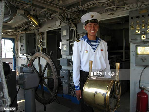 A naval seaman smiles from the bridge of the USS Pueblo a tourist attraction in Pyongyang North Korea August 31 2007 The ship was seized by North...