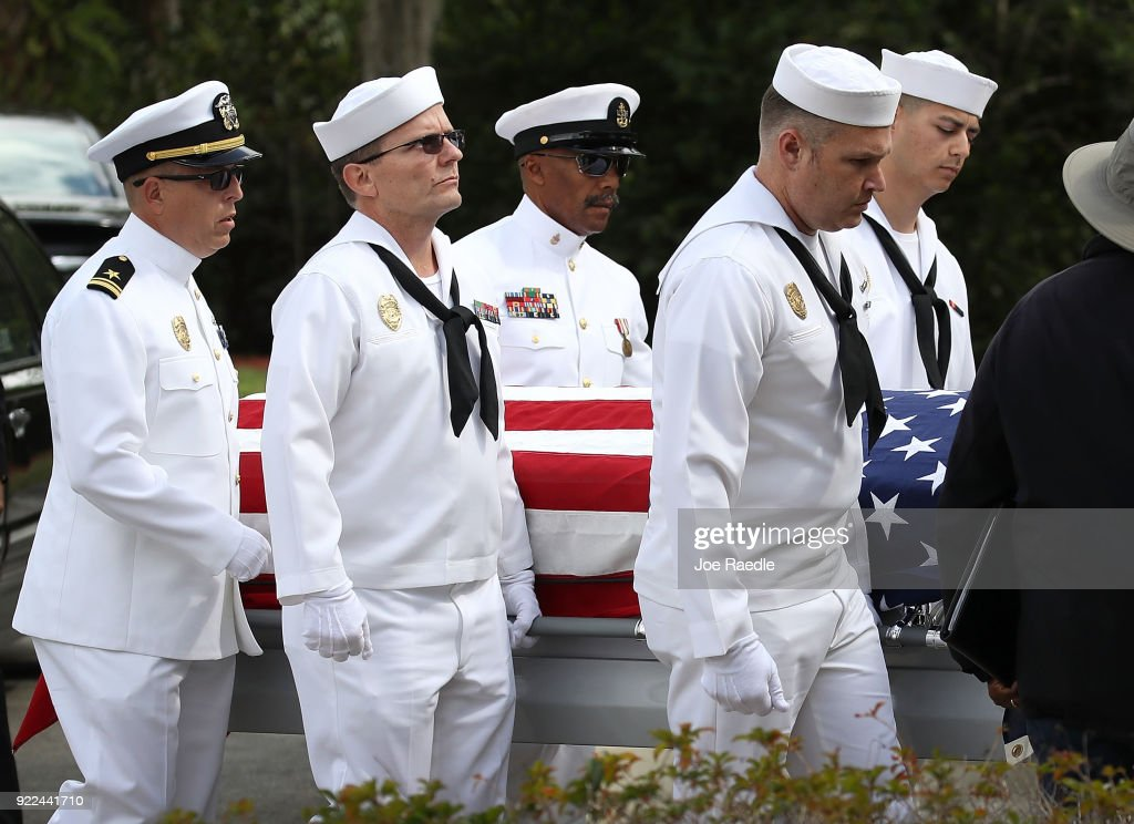 Naval Security Force Key West pallbearers carry the casket of Chris Hixon, who was the athletic director at Marjory Stoneman Douglas High School for his burial at South Florida National Cemetery on February 21, 2018 in Lake Worth, Florida. Police arrested 19 year old former student Nikolas Cruz for the killing of 17 people at the high school on February 14.