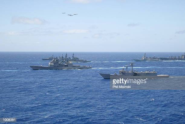 Naval ships from multiple nations steam in formation while a squadron of P3 ASW aircraft flies over during the RIMPAC excercise operations July 11...