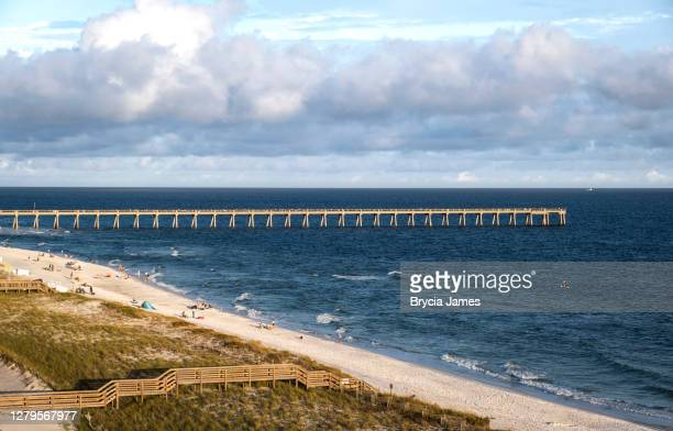 navarre beach with the pier in the background - brycia james stock pictures, royalty-free photos & images