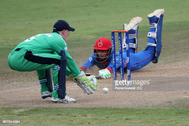 Naveen Ul Haq of Afganistan slides in with Ireland wicket keeper Mark Donegan waiting during the ICC U19 Cricket World Cup match between Afghanistan...