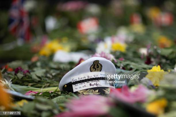 Navel cap sits amongst floral tributes to Prince Philip, Duke Of Edinburgh who died at age 99 outside of Windsor Castle on April 11, 2021 in Windsor,...