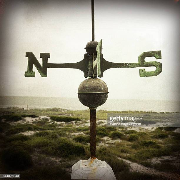 Navigational Compass In Grassy Area Near Sea Against Clear Sky