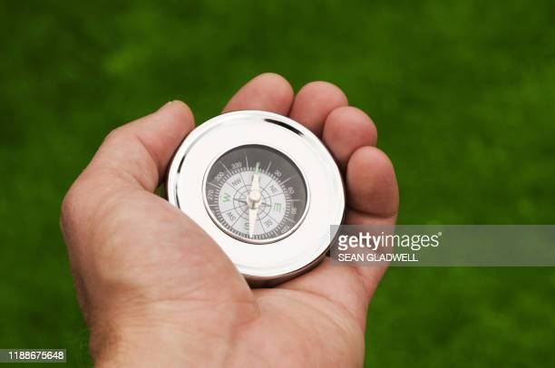 navigational compass in hand - compass stock pictures, royalty-free photos & images