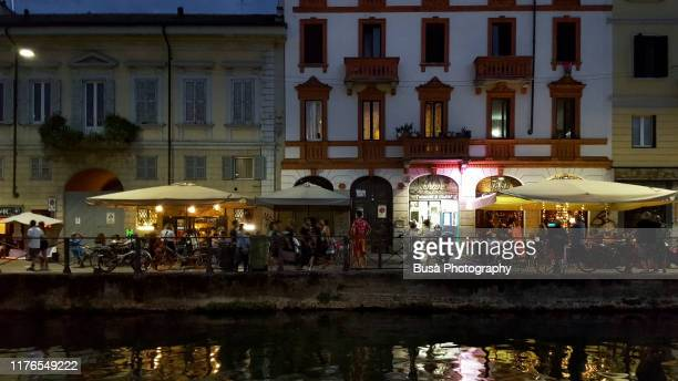 naviglio grande riverfront bustling with people at twilight. milan, italy - persona in secondo piano foto e immagini stock