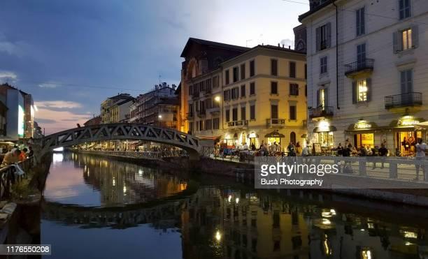 naviglio grande riverfront bustling with people at twilight. milan, italy - navigli milano foto e immagini stock