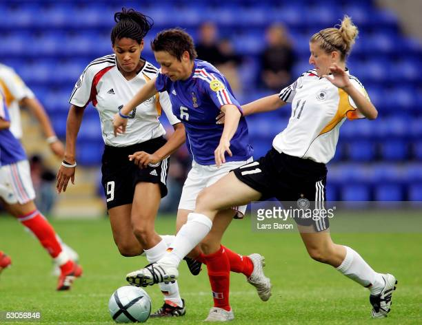 Navina Omilade and Anja Mittag from Germany challenge Sandrine Soubeyrand from France for the ball during the UEFA Women's EURO 2005 match between...