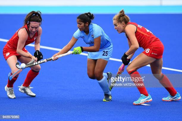 Navneet Kaur of India vies for the ball with England's Laura Unsworth and Emily Defroand during their women's field hockey bronze medal match of the...
