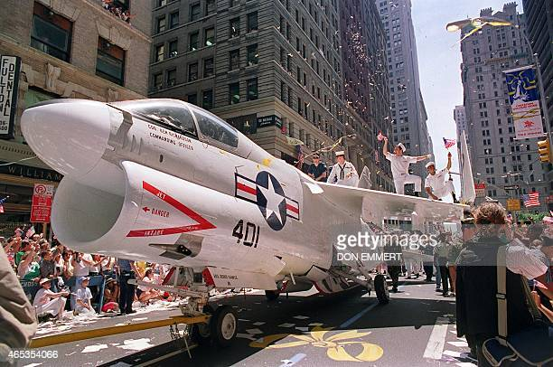 A Navy A7 Corsair jet is pulled down Broadway Avenue as sailors rejoice on the wings during the Operation Welcome Home tickertape parade during the...