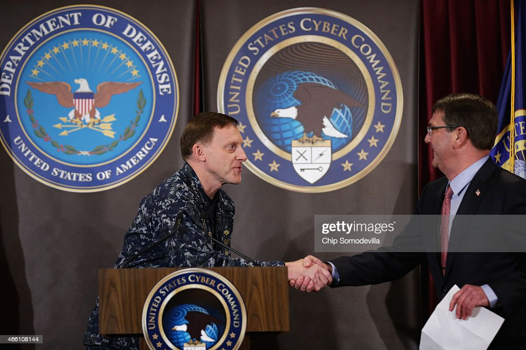 Navy Admiral Michael Rogers (L), commander of the U.S. Cyber Command and director of the National Security Agency, welcomes Secretary of Defense Ash Carter before an audience of NSA employees and troops at the agency and command headquaters March 13, 2015 in Fort Meade, Maryland. Carter emphasized the importance of military cyber operations by making this his first visit with soliders, sailors, airmen and Marines inside the United States since becoming defense secretary in February 2015.