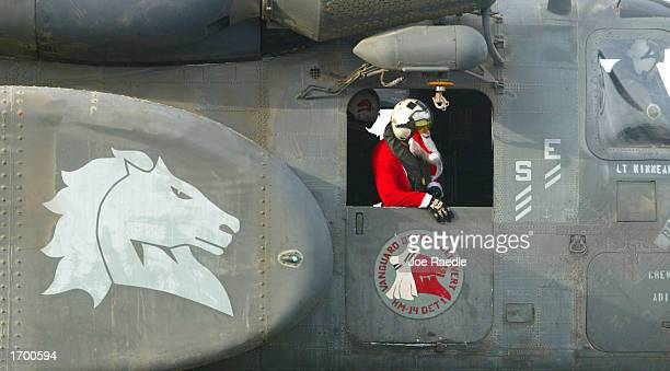 S Navy airman John Jacobs from Shirley New York dressed as Santa Claus looks out the gunners window of his Navy Sea Stallion as he delivers mail to...